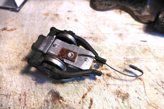 Aber die Lok braucht auch Strom vom anderen Rad. Also einfach nur einen Federkontakt von einer Kadee-Kupplung isoliert montieren.