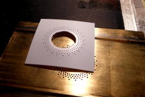 Eine der ersten geprägten Folien. Das Loch muss sein, damit sich das Polystyrolblatt besser ausdehnen kann.