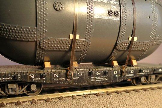 Die Befestigung des Behälters an den Rungen des Flachwagens - richtig mit Muttern gespannte Spanneisen an Widerlagern, die von unten in die Rungenhalterungen eingesteckt und von hinten mit Holzkeilen gesichert sind.