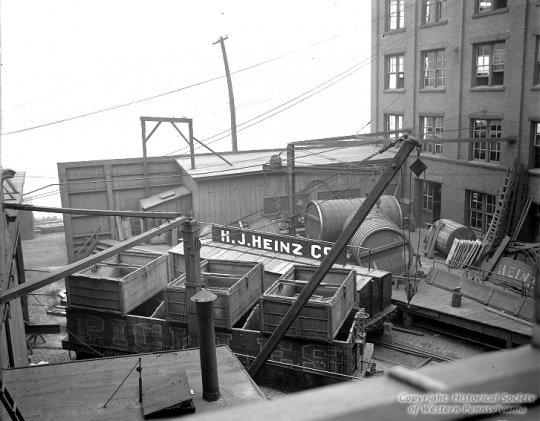 Wahrscheinlich eine Wagenwerkstatt der Firma Heinz. Im Vordergrund zwei der Pickle cars, jedoch in einer Vorgänger-Lackierung und im Hintergrund zwei Holztanks für die Essig-Wagen (vinegar). - Mit Genehmigung von ''H.J. Heinz Company Photographs, Detre Library & Archives, Sen. John Heinz History Center''