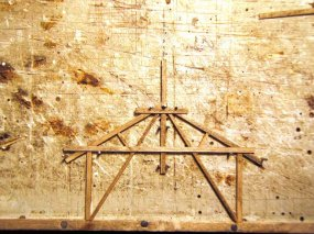 In einer Klebelehre werden die Dachbinder zusammengeklebt. Allerdings besteht diese Lehre nur aus Nägeln, die ich in die Arbeitsplatte geschlagen habe.