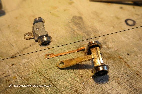 Nacharbeit! Oben die hintere Laufachse mit der viel zu kurzen Deichsel, wo auch kein Bleigewicht so richtig half. Unten die verlängerte Deichsel, bei der nun auch der Radsatz mit einer Feder auf's Gleis gedrückt wird!