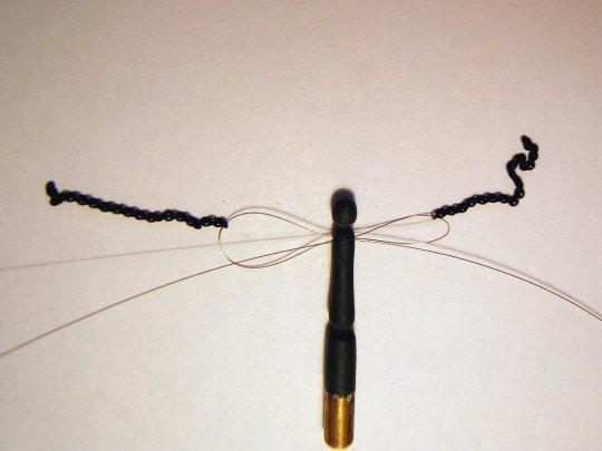Ein 0,3er Loch in Schulterhöhe gebohrt und Stahldraht 0,1 mm wie auf dem Bild dreifach hindurchgefädelt und dann ganz straff gezogen. Nicht vergessen, die Kettchen links und rechts in die Schlaufen einzuhängen!