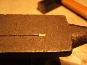 Das passende Material, Messing- oder Neusilberdraht mit 0,5 oder 0,6 mm Durchmesser - ein Ende mit scharfem Absatz über eine Kante ziemlich flach 'schmieden'.