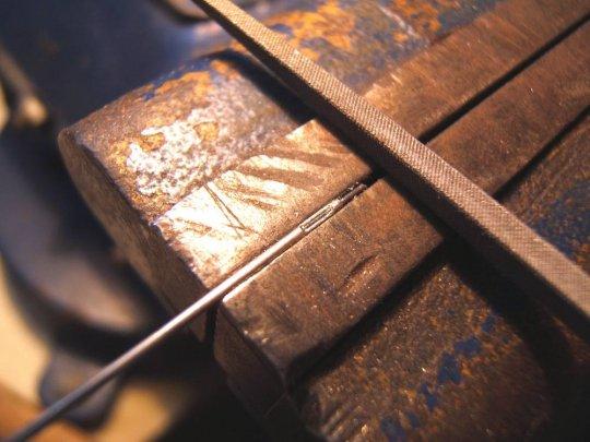 Den Stahldraht einfädeln und ein Auge feilen, bis der Stahldraht die weitere Bearbeitung hemmt. Eventuell die Breite des Auges auf Wunschmaß verbreitern.