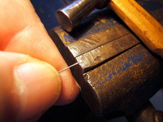 An die beiden Spannstangen muss nun jeweils ein Ende breit geschlagen werden. Diese 'Köpfe' sollten danach vom Ende her auf das unbedingt notwendige Maß zurückgefeilt werden, so dass sie klein sind, aber nicht durch das Rörchen hindurchgezogen werden können.