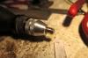 ... die dann in der von Hand geführten Bohrmaschine über dem fixierten Schleifpapier zur runden Scheibe geschliffen wird.