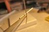 Aus dem dünnen Bleichstreifen ist ein Fußverbinder herzustellen, der in der Realität ein Zuführungsrohr zu den seitlich angeordneten Lampen ist. Mit einer scharfkantigen Flachzange ist ein Auge um ein Rohrstück mit 1,4mm Durchmesser zu biegen. Die Breite des Mauls bestimmt dabei den Abstand der Lampen von dem mittig angeordneten Behälter.