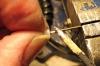 Fixieren Sie im Anschluss den Dorn in einem Schraubstock oder mittels eines sogenannten Dritte-Hand Gerätes fixieren und erwärmen Sie den Dorn in der Nähe des Lampenschiermes mit einem Lötkolben, so können Sie den Lampenschirm von dem Dorn vorsichtig abziehen. Durch die Wärme des Dorns wird der Sekundenkleber wieder weich und die Verklebung löst sich. Achtung! Den Lampenschirm sauber axial, also in Richtung der Achse des Dornes abziehen, damit sich die Bohrung nicht verkantet.
