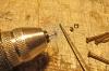 Der nächste Schritt ist die Anfertigung von ''Lampenkronen'', die oben auf die Lampenschirme aufgesetzt werden. Da diese Teile absolut an oberster Stelle unter den Dach angeordnet sind, habe ich einen sehr einfachen Weg der Herstellung gewählt. Im Baumarkt waren entsprechende Nägel aus Messing mit rundem Kpof und einem Durchmesser von 3 mm im Angebot, die ich für geeignet hielt. Es könnten wohl ebenso MS-Holzschrauben oder ähnliches sein. Entscheidend ist, dass der Scaht unter dem Kopf wieder mit der Handbohrmaschine einen Schaft von etwas unter einem Millimeter erhält, damit er in die Bohrung im Lampenschirm eingestreckt werden kann. Die Länge ist kurz zu halten, kann jedoch nachfolgend noch bearbeitet werden.