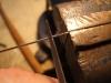 Den Stahldraht im Schraubstock einspannen und dann bei langsamer Drehung der Kanüle mit einer Dreikantfeile ringsum eine feine Kerbe feilen. Die Kerbe muss nicht bis auf den Stahldraht gefeilt werden, so dass man sich die Feile ruinieren würde.
